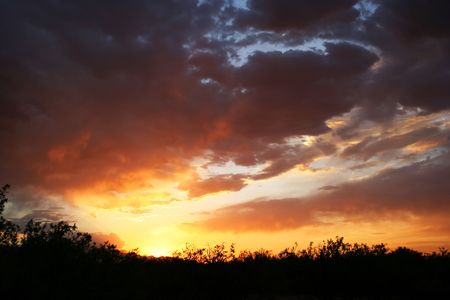 The sun sets in a cloudy sky over a mesquite bosque in southeastern Arizona setting the sky on fire. Stock Photo