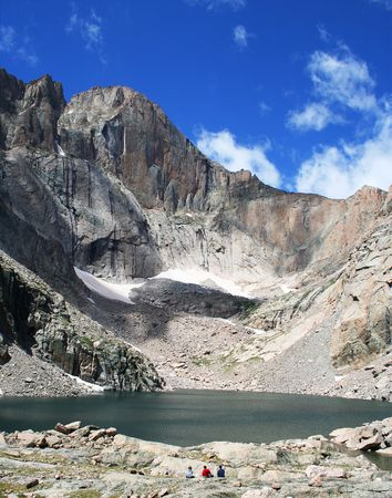 Three hikers view Chasm Lake, at the base of Longs Peak, Rocky Mountain National Park, Colorado Stock Photo