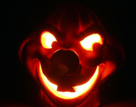 glows: This horrid Halloween hobgoblin glows menacingly on a pitch black Halloween night. Stock Photo