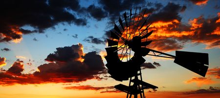 This old windmill contrasts dramatically against a fiery Arizona sky at dusk. photo