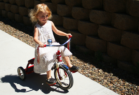 This three-year-old pixie just loves showing off her new tricycle.