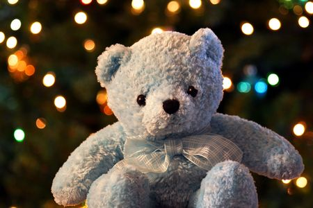 A blue teddy bear sits before a background of shimmering Christmas tree lights photo