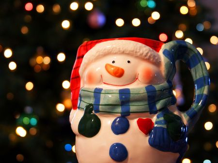 A single cheerful snowman mug rests before a background of shimmering Christmas tree lights photo