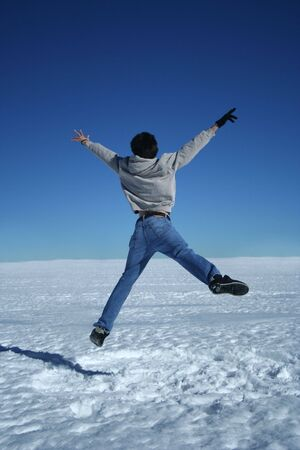 exhilaration: A young man shows his exhilaration at seeing the winter snow by leaping high for joy
