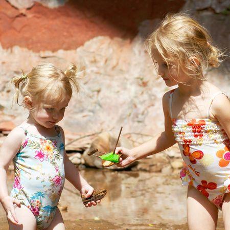 이 4 살짜리 픽시는 크릭에서 자매 여동생과 수제 보트를 나누는 것을 아주 좋아합니다. 스톡 콘텐츠