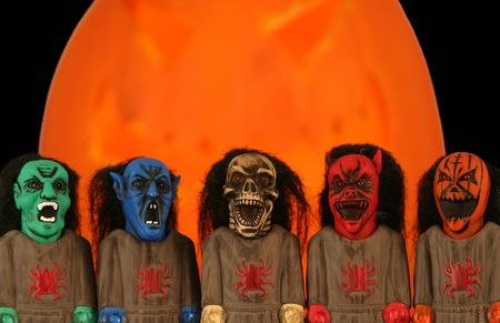 menacing: A Gang of Five Monsters Stands Before a Giant Jackolantern on Halloween Night Stock Photo