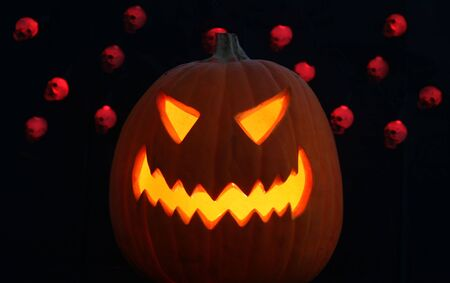 A lone jack-o-lantern grins maniacally on a pitch black Halloween night, red disembodied skulls dance in the background  Stock Photo