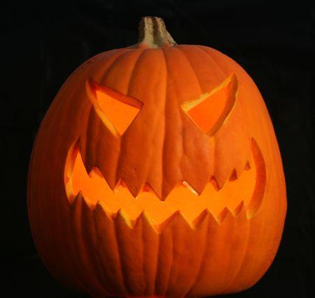 A scary jack-o-lantern grins maniacally on a pitch black Halloween night. photo