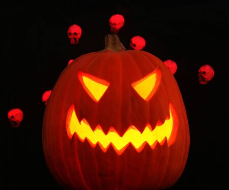 A scary jack-o-lantern grins maniacally on a pitch black Halloween night, red skulls dancing behind 免版税图像