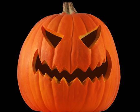 grins: A lone jack-o-lantern with black eyes and mouth grins maniacally on a pitch black Halloween night.