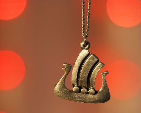 A Viking Ship Necklace Against Red Lights