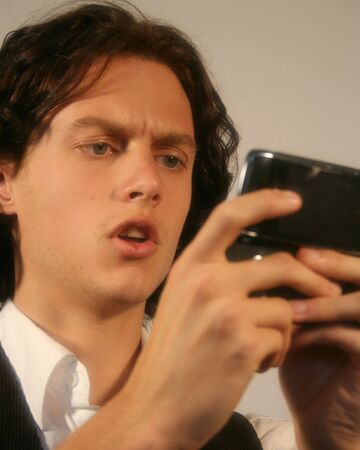 long nose: A Handsome Young Man Gets Distressing News on His Cell Phone Stock Photo