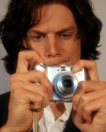 long nose: A Handsome Teen Takes a Picture with a Digital Camera Stock Photo