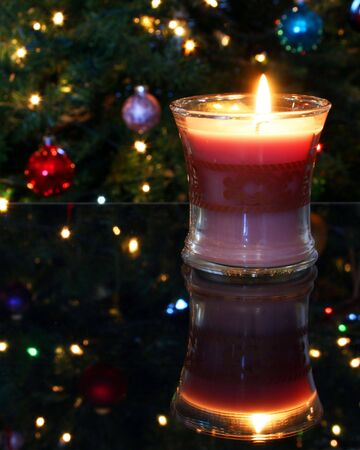 reflects: A Christmas Candle on a Glass Table Reflects a Tree Stock Photo