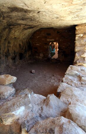 the dwelling: A Woman Inspects a Sinagua Dwelling in Walnut Canyon National Monument, Arizona Stock Photo