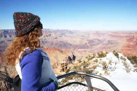 A Woman in a Colorful Cap Gazes at the Grand Canyon in Winter photo