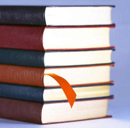 An Orange Bookmark and a Set of Six Leather Bound Books Фото со стока