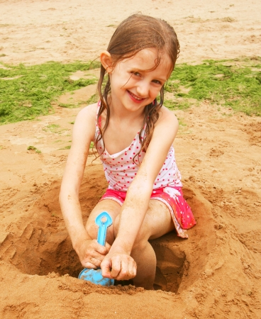 A Little Brunette Girl in a Pink Polkadot Swimsuit Playing in the Sand at the Beach Stock Photo - 7561126