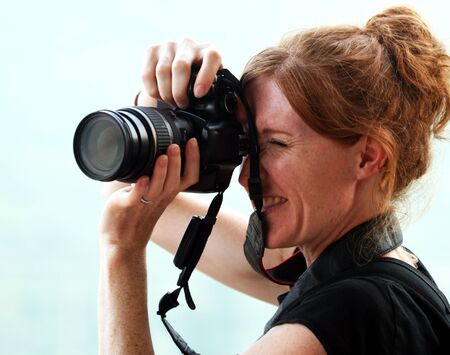 poised: A Beautiful Female Photographer with Red Hair is Poised with Her Camera