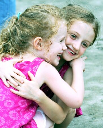kids hugging: A Pair of Little Blonde Sisters Laugh and Embrace Stock Photo