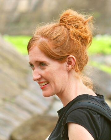 A Portrait of a Beautiful Smiling Redheaded Green Eyed Woman Outdoors