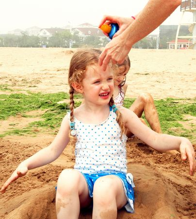 A Little Girl Doesn't Like Mommy Spraying Her with Sunscreen at the Beach 스톡 콘텐츠
