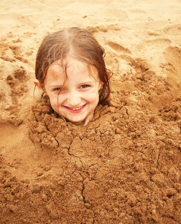 bury: A Little Girl Buried in the Sand at the Beach