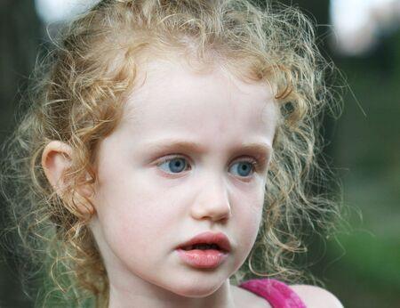 Een klein meisje met grote blauwe ogen en krullen in haar haar  Stockfoto