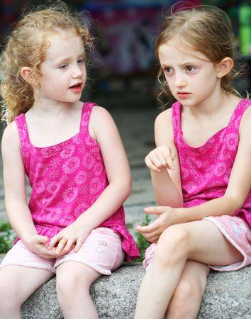 Een paar kleine blonde zusters hebben een gesprek