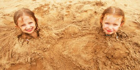 A Pair of Sisters Buried in the Sand at the Beach photo