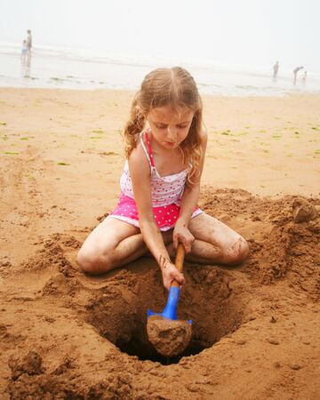 dug: A Little Girl in a Pink Polkadot Swimsuit Digging at the Beach with a Blue Shovel