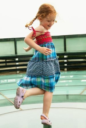 A Little Girl Dances in a Red and Turquoise Dress Stock Photo