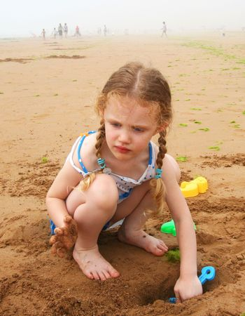 파란색 삽으로 해변에서 파고 파란색 Polkadot 수영복에 어린 소녀
