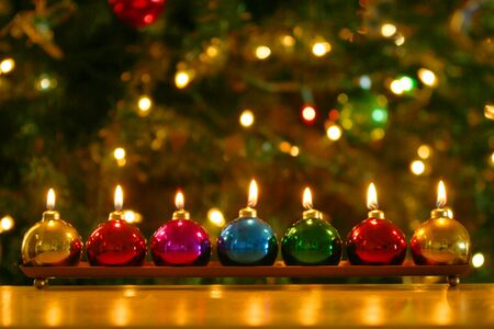 greeting season: A Line of Seven Burning Christmas Ornament Candles Stock Photo