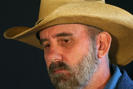 A Bearded Cowboy Against Black With a Sad, Pensive Expression photo