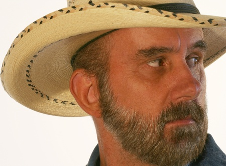 A Bearded Cowboy Against White Glances Over His Shoulder photo