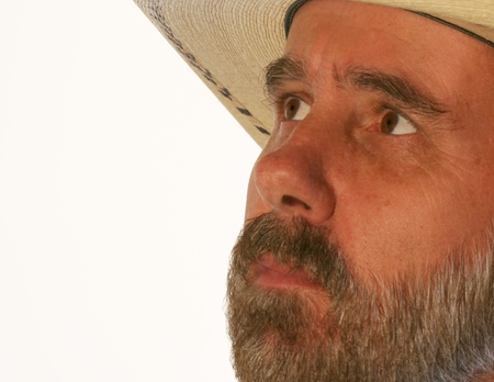 A Bearded Cowboy in a Straw Hat Looks Up Against White photo