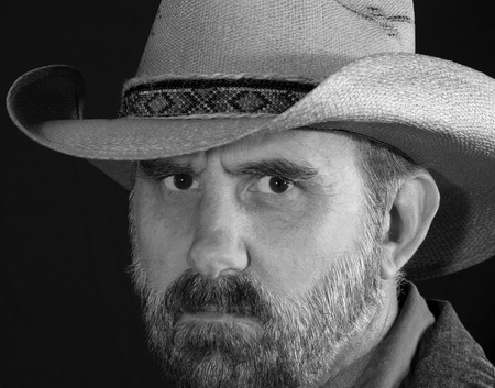 frowns: A Bearded Cowboy with a Stern Frown in Black and White Stock Photo