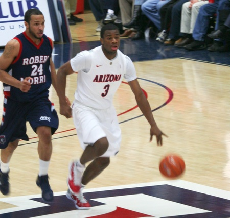 A Defender Chases Kevin Parrom in a University of Arizona Wildcats Men's Basketball Game Against the Robert Morris Colonials at McKale Center, Tucson, on December 22, 2010. Lawrence Bridges. Stock Photo - 8577360