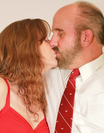 A Middle Aged Married Couple in Red Dress and Red Tie Kissing photo