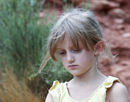 A Sad Little Girl with Wispy Blonde Hair in a Yellow Top