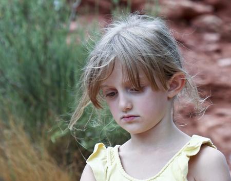 caras tristes: Una niña triste con tenues rubia en un Top amarillo Foto de archivo