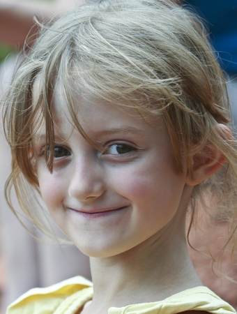 A Close Up Portrait of a Little Smiling Girl with Wispy Blonde Hair