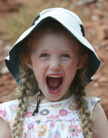組み紐とフロッピーの白い帽子の小さな悲鳴している女の子