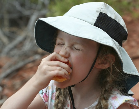 A Little Girl in Braids and a Floppy White Hat Eating a Peach