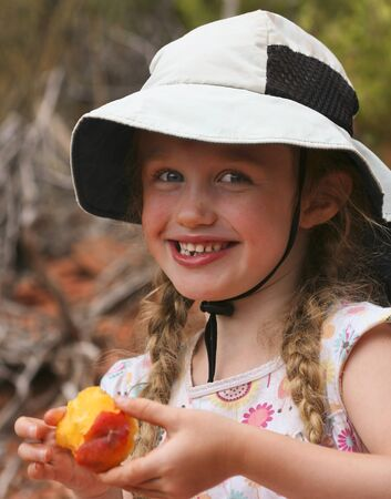 A Little Smiling Girl in Braids and a Floppy White Hat with a Peach