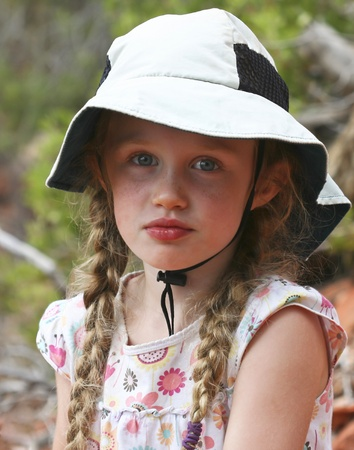 A Little Blue Eyed Girl in Braids and a Floppy White Hat