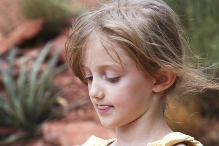 A Determined Little Girl Sticks Out Her Tongue as Her Wispy Hair Blows in the Breeze photo