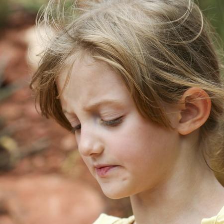 ojos tristes: Una niña fruncidos labios y mirada abatido muestra decepción Foto de archivo