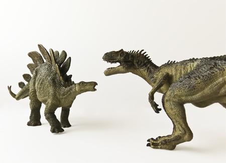battling: A Stegosaurus and Allosaurus Battle Against a White Background